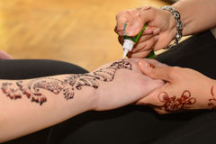Henna tattoos on hands. Person makes henna tattoos on hands - close-up stock photo