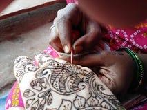 Hennamehendi bij hand het Indische tatoegering maken stock foto