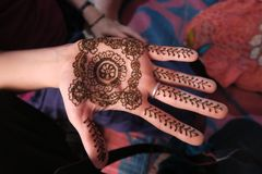 Hennastrauchkunst: gemalte Hände mit schwarzer traditioneller Farbe in einem indischen Haus lizenzfreie stockfotografie