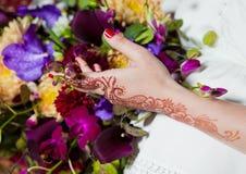 Hennastrauchtätowierung auf den Händen, die bunte Blumen halten, mischen Stockbild