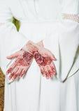 Hennastrauchtätowierung auf den Händen, die an weißes Kleid halten Lizenzfreie Stockbilder