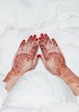 Hennastrauchtätowierung auf den Händen, die an weißes Kleid halten Stockfotografie