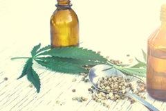 Hennepbladeren op houten achtergrond, zaden, de uittreksels van de cannabisolie in kruiken stock fotografie