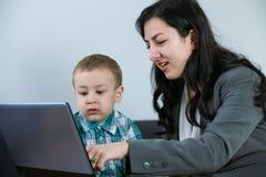 Hennes moderuppvisning behandla som ett barn pojken något på datorskärmen Arkivbild