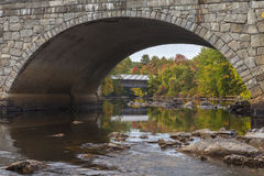 Henniker Bridges in Autumn. The Henniker wooden covered bridge can be seen through the arch of the new bridge through town. The covered bridge is now used as a royalty free stock image