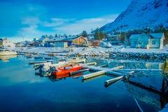 Henningsvaer,挪威- 2018年4月04日:小渔船室外看法在一个捕鱼港口的与山反射 图库摄影