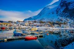 Henningsvaer,挪威- 2018年4月04日:小渔船室外看法在一个捕鱼港口的与山反射 免版税库存图片