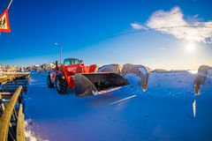 HENNINGSVAER,挪威- 2018年4月10日:用雪报道的红色拖拉机室外看法在一个晴天在a的wniter期间 库存图片