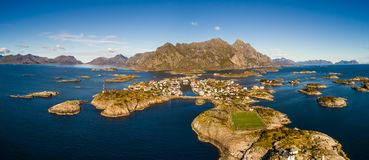 Henningsvaer fishing village on Lofoten islands from above. Aerial view of Henningsvaer, its scenic football field and mountains in the background. Henningsvaer Stock Photography