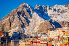Henningsvaer Norwegia, Kwiecień, - 04, 2018: Malowniczy połowu port w Henningsvaer z typowymi czerwonymi drewnianymi budynkami i Obraz Stock