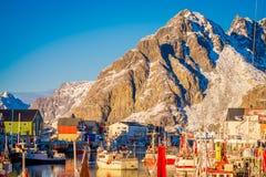 Henningsvaer Norwegia, Kwiecień, - 04, 2018: Malowniczy połowu port w Henningsvaer z typowymi czerwonymi drewnianymi budynkami i Zdjęcia Royalty Free