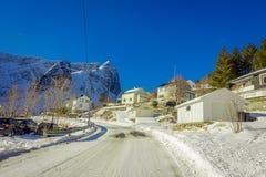 Henningsvaer Norwegia, Kwiecień, - 04, 2018: Plenerowy widok drewniani domy przy jeden stroną droga zakrywająca z śniegiem a Fotografia Royalty Free