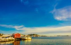 Henningsvaer Norwegia, Kwiecień, - 04, 2018: Plenerowy widok drewniany budynek w zatoce z łodzią przy brzeg w Lofoten wyspach Zdjęcia Royalty Free