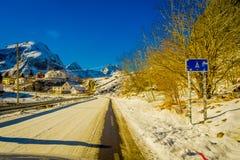 Henningsvaer Norwegia, Kwiecień, - 04, 2018: Plenerowy widok pouczający znak z drewnianymi domami przy jeden stroną droga Zdjęcia Royalty Free