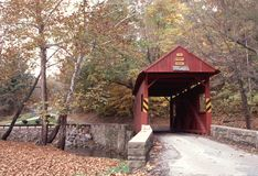 Henry Bridge, PA. Old time red, wooden covered bridge in Pennsylvania countryside nestled among autumn trees Royalty Free Stock Image
