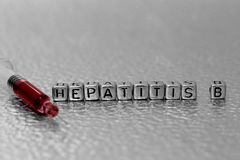 Hepatitis B on beads with blood in a syringe. On a metal background royalty free stock photography