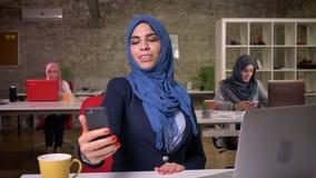 Heppy arabska kobieta bierze selfie na jej telefonie podczas gdy siedzący w krześle w ceglanym biurze z innymi muzułmańskimi dzie