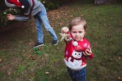 快活的圣诞节节日快乐 女孩heps她的装饰圣诞树的父亲室外在房子bef的围场 免版税库存图片