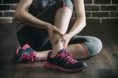 Her ankle injured in gym fitness exercise training, healthy life Stock Photo