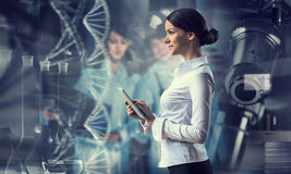 Her biochemistry research and discovery. Mixed media. Elegant businesswoman scientist with tablet in hands. Mixed media Royalty Free Stock Photography