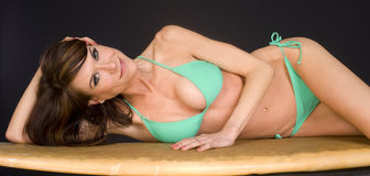 On Her Board Woman Lays on Well Worn Surfboard Royalty Free Stock Image