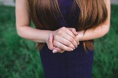 Her clasped hands girls. Nature background green purple Stock Photo