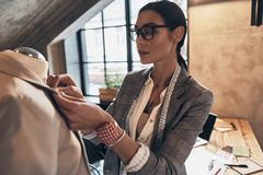Her design is perfect. Serious young woman in eyewear adjusting. A collar of the jacket on mannequin while standing in her workshop Stock Photos