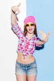 Her energy charges. Playful young woman in headwear and glasses gesturing and looking at camera while standing against colorful background Royalty Free Stock Photos