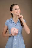 Her first savings. Pretty teenage girl holding a piggy bank and Royalty Free Stock Photo