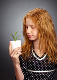 Her Future. Pretty girl holds a young plant and looks at it thoughtfully royalty free stock photos
