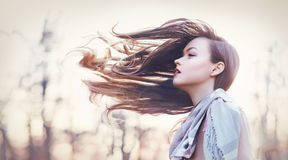 Her hair tooked by the wind. Beautiful young woman autumn evening her hair tooked by the wind and fly before her Fashion toning royalty free stock images