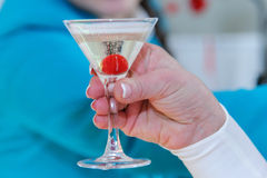 In her hand a glass of champagne with a cherry inside. Berry cherry in champagne. Luxurious party. Noble alcohol at a gala Banquet Royalty Free Stock Photography