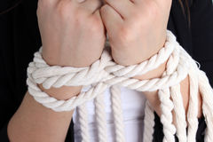 Her hands tied with a rope. Girl with a white blouse and black jacket Stock Photos