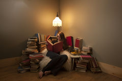 Her Happy Place. A young woman sitting in her reading spot surrounded by her favourite things - books Stock Photography
