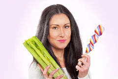 Her healthier choice. Pretty woman choosing between celery and candy Royalty Free Stock Image