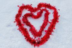Two red hearts in the snow made of christmas wires. Her heart inside his heart in the snow, to remember Valentine`s Day Royalty Free Stock Photos