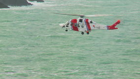 Her Majesty's Coastguard helicopter hovering in position stock footage