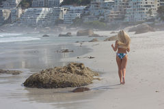 Her Morning Jog. Back-view of attractive blonde in a bikini running on the beach Royalty Free Stock Photography
