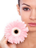 Her radiant beauty is the product of great skin care. Cropped shot of a beautiful young woman holding flower isolated on white Royalty Free Stock Photography