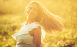 Her smile speaks of happiness. Happy woman on field. Close up royalty free stock photo