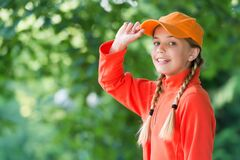 Her style is a lot more casual. Happy child in casual style natural outdoors. Little girl wear baseball cap. Casual