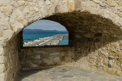 HERACLION, GREECE - November 2017: View of the pier through the embrasure of old Venetian fortress Koule, Crete,. HERAKLION, GREECE - November, 2017: Embrasure royalty free stock photography