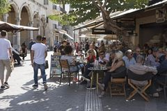 Diners and drinkers in a crowded bar in Heraklion, Crete, Greece. Heraklion, Crete, Greece. A busy bar taverna on the Platia Venizelou in the  Iraklio city Stock Image