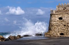 Heraklion, Crete - Greece. Sea waves hitting the breakwaters next to the fortress Koules at the old port of Heraklion city. Sunny. Day with blue cloudy sky royalty free stock photo