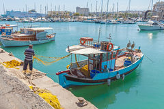 HERAKLION, GREECE - AUGUST 3, 2012: Fishermen working with old n Royalty Free Stock Photos