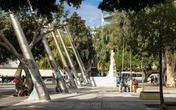 HERAKLION, GREECE - November, 2017: The central square. Crete, Greece - November, 2017: Elderly people resting in the shade of trees in the central square of the Stock Photos