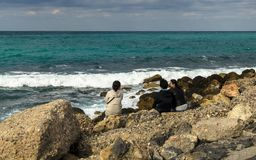 HERAKLION, GREECE - November, 2017: Tourists resting on the stones by the sea near old Venetian fortress, Heraklion port, Crete. HERAKLION, GREECE - November Royalty Free Stock Photography