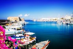 Old port of Heraklion, Crete, Greece. Heraklion old venetian harbour with colorful small fishing boats, yachts and ships, Heraclion Crete, Greecer with flowers Royalty Free Stock Photos
