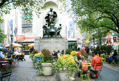 Herald Square Park in New York City. People eat and converse under the memorial to the founders of the New York Herald Tribune where Broadway and Sixth Avenue Stock Photography