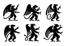 Heraldic griffins with raised paws. Ancient heraldic griffins symbols of black majestic beasts with body of lion, angel wings and eagle heads. For heraldic Stock Photos